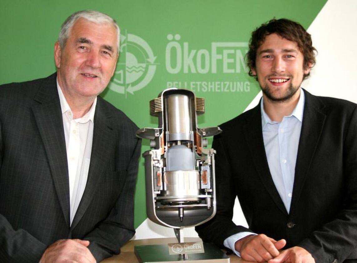 Die ÖkoFEN-Geschäftsführer Herbert Ortner (li.) und Stefan Ortner (re.) mit einem Modell des Stirlingmotors, der erstmals die serienreife Ökostromerzeugung mittels einer Pelletsheizung ermöglichen soll.