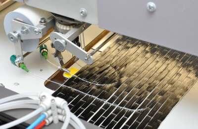 Die empfindliche Faser wird durch Sticken im Textil befestigt und später durch Epoxidharze fixiert (Bild: Dr. Kuhne, MFPA Weimar)