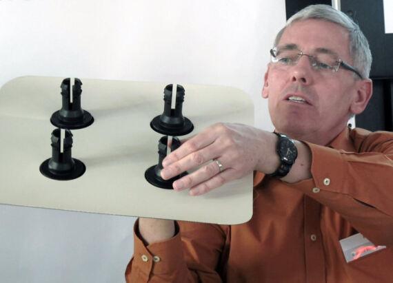 Vertriebs- und Marketingleiter Gerhard Einsele stellt hier während einer Pressekonferenz auf der Dach+Holz die Fixierplatte und die Manschette des SOLfixx-Systems vor.