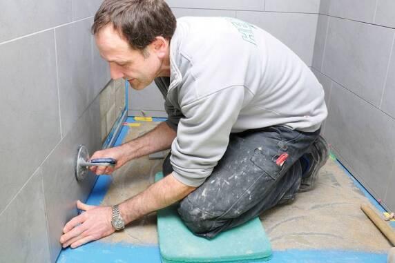 Zuletzt werden die ausstehenden Fliesenarbeiten durchgeführt. Dabei werden die Wandfliesen für nahtlose Übergänge bis in das Duschboard gelegt.