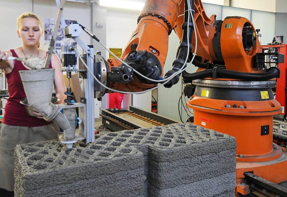 An der Versuchsanlage für additive Fertigung wird durch Extrusion von Holzleichtbeton ein Wandelement hergestellt. Studentin Bettina Saile befüllt den Versuchsextruder mit Frischbeton. (Foto © K. Henke / TUM);